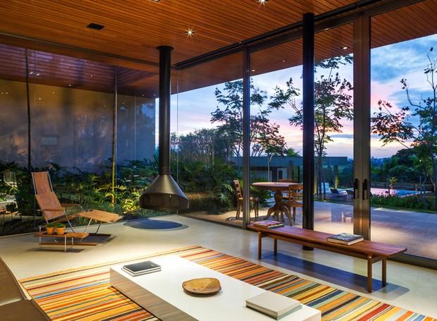LIVING | Com paredes de vidro, a sala tem lareira flutuante, da Construflama. Poltrona, mesa lateral e mesa de centro, da Casual. Tapete By Kamy (Foto: Rafaela Netto/Divulgação)