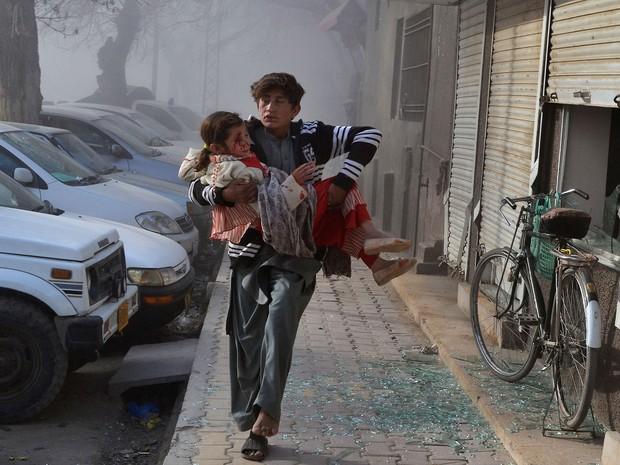 Jovem carrega garota ferida em atentado neste sábado em Quetta, no Paquistão (Foto: Arshad Butt/AP)