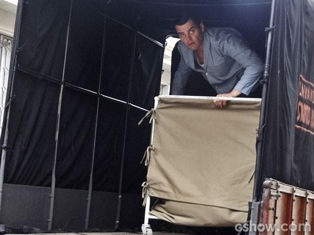 Manfred se esconde dentro do carrinho de roupa suja (Foto: Joia Rara/TV Globo)