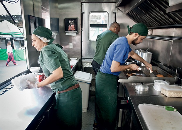 OPORTUNIDADE O publicitário Doni Nascimento (de azul) na cozinha  do Le Camion.  O food truck virou  opção de carreira (Foto: Letícia Moreira/ÉPOCA)