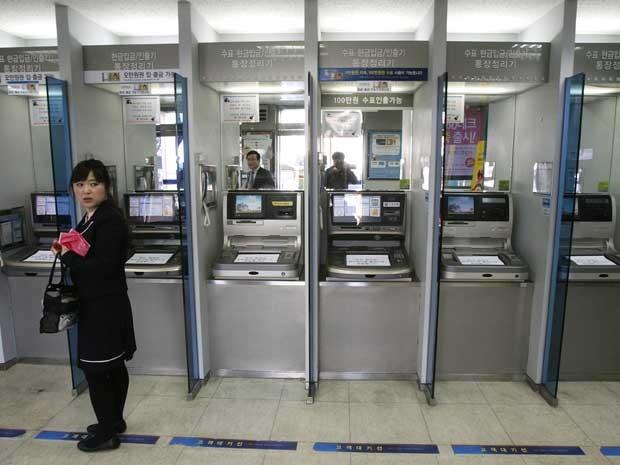 Cliente na frente de caixas automáticos de uma agência do Banco Shinhan, em Seul, durante 'apagão' nos servidores da instituição financeira. (Foto: Ahn Young-joon / AP Photo)