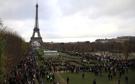 Ativistas se reúnem em Paris, França, para comemorar o primeiro acordo global contra as mudanças climáticas (Foto: Thibault Camus/AP)