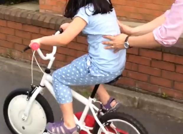 Com auxílio do pai, garotinha faz teste da Jyrobike (Foto: Reprodução/YouTube)