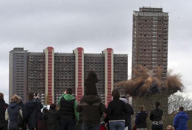 Pessoas assistem implosão de prédio em Glasgow neste domingo (5) (Foto: David Cheskin/AP)