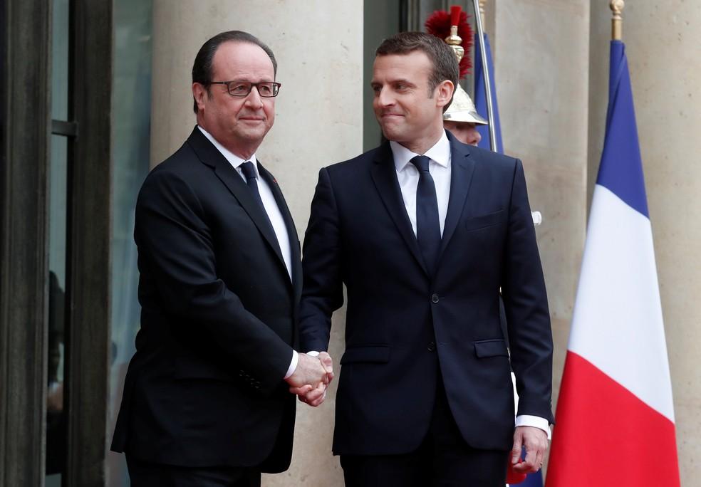 Macron e Hollande se cumprimentam na chegada do novo presidente ao Palácio do Eliseu para a cerimônia de posse neste domingo (14) (Foto: Benoit Tessier/Reuters)