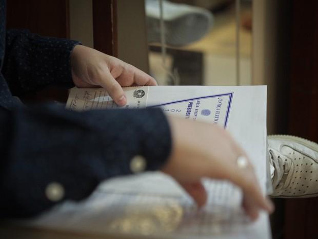 Neto do mesário mais antigo do estado de São Paulo, Bruno se examina os comprovantes de votação que o avô guardava com carinho em uma pasta (Foto: Caio Kenji/G1)