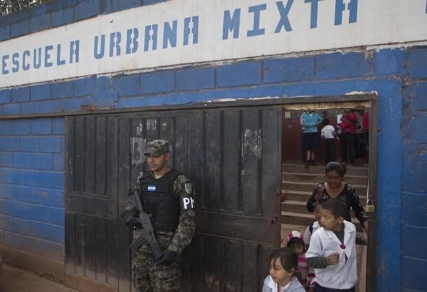 Policial militar faz guarda em frente a escola no última dia de aulas na capital Tegucigalpa (Foto: Esteban Felix/AP)