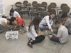 Crianças autistas trabalham em grupo para montar robôs (Foto: Reprodução/TV TEM)