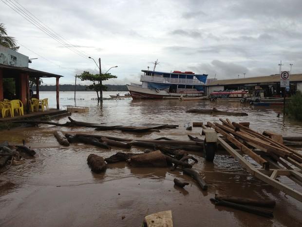 Rio está acima do nível de transbordamento.  Comércio de Ronaldo Garcia já tem água na calçada (Foto: Ivanete Damasceno/G1)