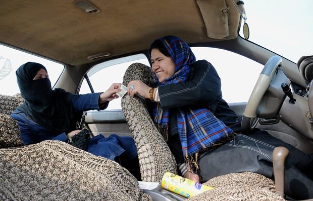Cliente paga corrida no taxi de Sara Bahai, em Mazar-e Sarif, no dia 3 de março (Foto: Mustafa Najafizada/AP)