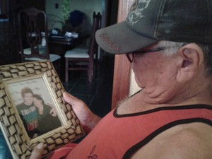 Triste ao ver filho preso pai de Hudson observa foto de filho com a mãe (Foto: Fernanda Zanetti/G1)