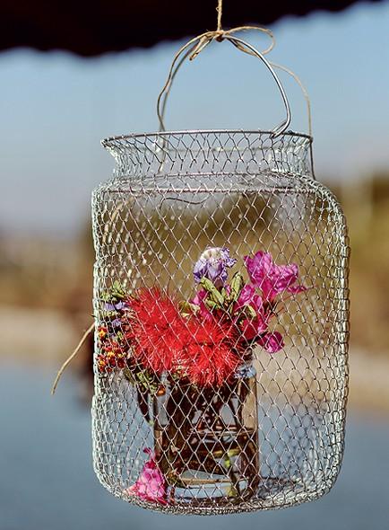 Em vez de peixes, o samburá pendurado recebeu um vasinho de flores. Boa pedida para festas ao ar livre
