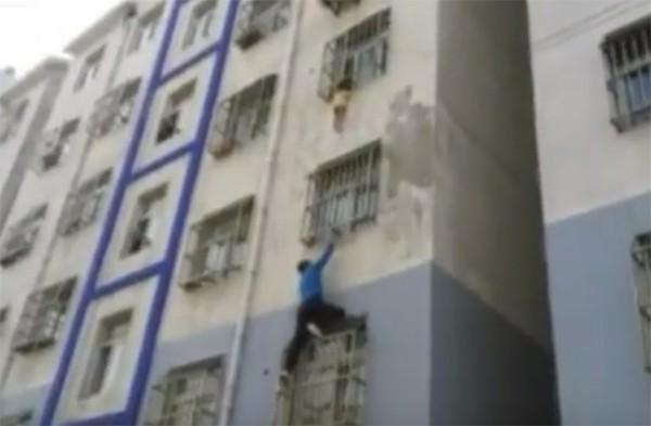 Chinês salva menino preso na grade de janela de apartamento (Foto: Reprodução / YouTube)