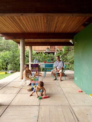 À esq., Grazi e Leandro olham raul brincar na varanda, que tem painel de Formica de lousa (à dir.). Na mesa, lanternas, da Benedixt, passadeira, da reciclamundo, e bandeja e taças, da regatta casa. cadeira Technicolor, da Tidelli (Foto: Victor Affaro)