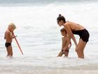 Com vestido transparente, Fernanda Lima brinca com os filhos à beira-mar