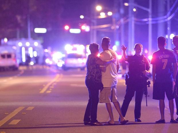 Policial orienta família a ficar longe da boate alvo do atirador em Orlando, nos Estados Unidos (Foto: Phelan M. Ebenhack/AP Photo)