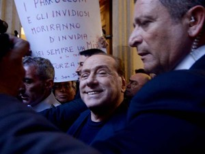 Silvio Berlusconi sorri ao chegar nesta quarta-feira (11) em sua casa em Roma cercado por seguranças (Foto: AFP PHOTO / FILIPPO MONTEFORTE)