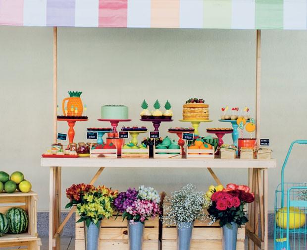 A mesa | Uma barraca de madeira coberta com um toldo de lona listrado fez as vezes da mesa. Bandejas de cores vibrantes e de diferentes alturas acomodaram as Guloseimas em formato de frutas. Na lateral, pallets com laranjas e melancias e, à frente, vasos  (Foto: Thais Galardi/GNT)