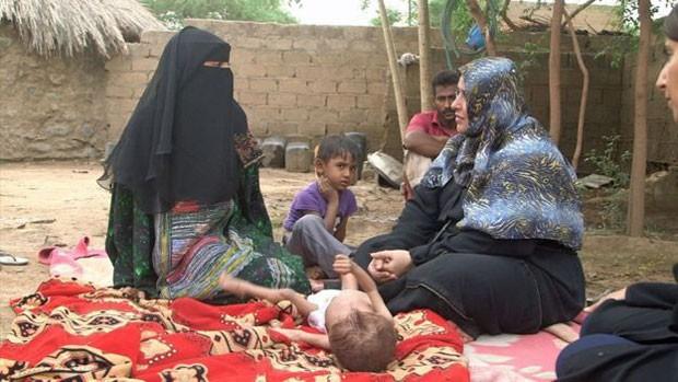 Ashwaq Muharram segura a mão de Abdulrahman, que tem 18 meses, mas o mesmo peso de um bebê de 6. (Foto: BBC)