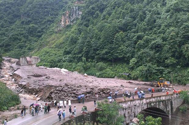 Pessoas olha estragos causados por deslizamento de terra na China nesta quarta-feira (9). 17 pessoas desapareceram (Foto: China Daily/Reuters)