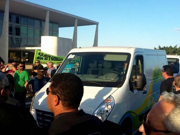 Vans do Comitê Organizador Rio 2016 cercadas por policiais civis do Distrito Federal, durante ato em frente ao Palácio do Planalto (Foto: Pedro Borges/G1)
