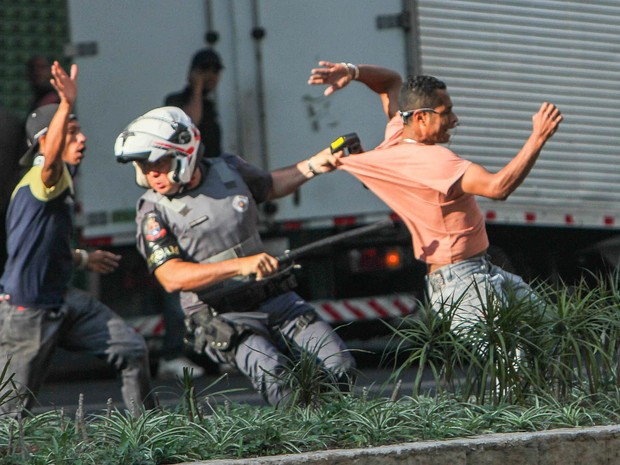 Policial tenta deter homem se envolveu em confronto durante reintegração de posse na Avenida São João, Centro de São Paulo (Foto: Marco Ambrosio/Estadão Conteúdo)