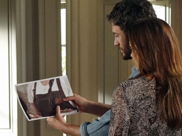 O rapaz analisa a foto  (Foto: Amor Eterno Amor/ TV Globo)