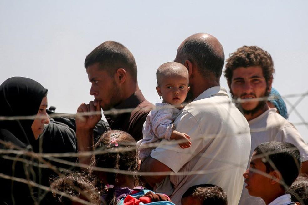 Sírios que se deslocaram para fugir do Estado Islâmico se instalam em campo de refugiados na cidade de Ain Issa  (Foto: Delil Souleiman / AFP)