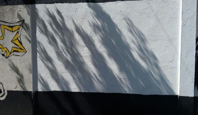 Muro do CT Rei Pelé é pintado de branco no local onde imagem de Robinho foi vandalizada (Foto: Lucas Musetti)