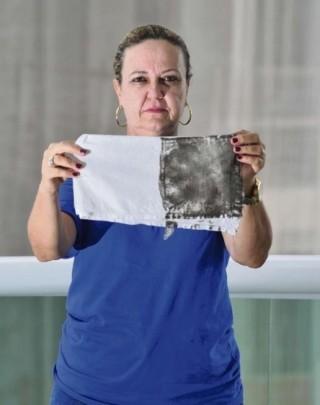 Dona de casa mostra pano após limpar casa (Foto: Marcelo Prest/ A Gazeta)