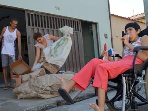 Rosinha espera na cadeira enquanto a mãe coleta os materiais (Foto: Fernanda Zanetti/G1)