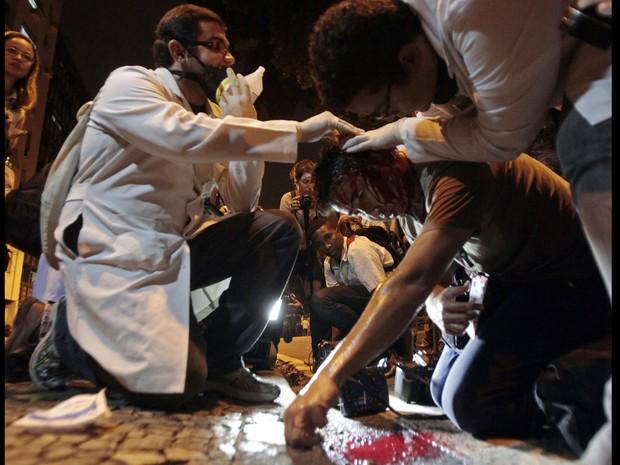 Yasuyoshi Chiba, da AFP, recebe ajuda após ser ferido na cabeça. Segundo ele, um policial militar o atingiu com um cassetete (Foto: Sergio Moraes/Reuters)