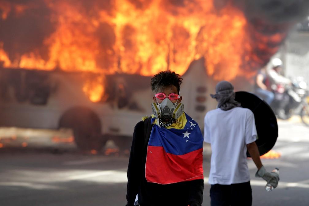 Ônibus foi incendiado neste sábado (13), em Caracas, durante protesto contra o presidente Nicolas Maduro (Foto: REUTERS/Christian Veron)