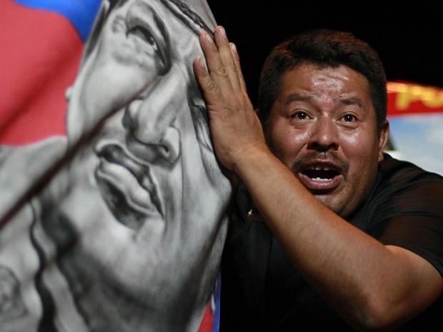 Eleitor de Maduro comemora o resultado com uma bandeira mostrando a face de Chávez, em San Salvador (Foto: Ulises Rodriguez/Reuters)