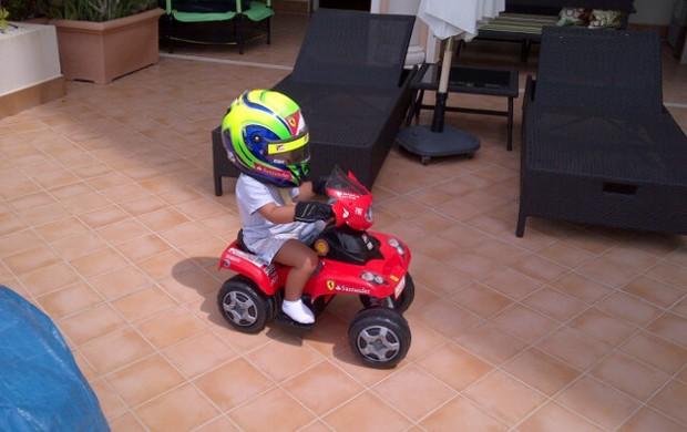 Felipinho, filho de Felipe Massa brinca em carrinho da Ferrari com capacete do pai (Foto: Reprodução/Twitter)