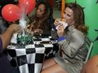 De pernas de fora, Viviane Araújo devora salgadinho em festa