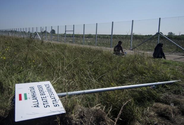 Migrante ficam atrás de cerca na fronteira da Hungria com a Sérvia (Foto: Csaba Segesvari / AFP)