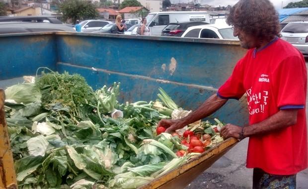 Miguel Romão da Silva, selecionando alimentos descartados na caçamba da feira de Brás Cubas, em Mogi das Cruzes (Foto: Jamile Santana/ G1)