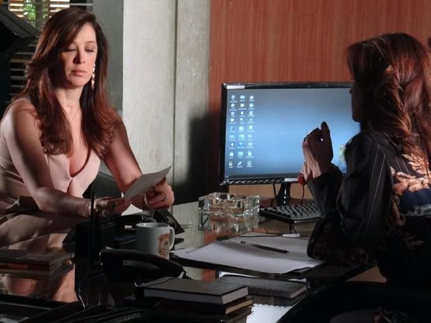 Lívia finge que não reconhece Russo nas fotos (Foto: Salve Jorge/TV Globo)