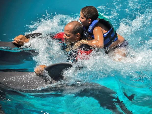 Adrian e Javier 'surfam' em golfinhos (Foto:  AFP Photo/Adalberto Roque)