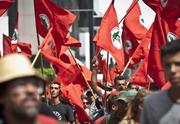 Manifestantes seguram bandeiras do Movimento dos Sem Terra (MST) (Foto: Marcelo Camargo/Agência Brasil)