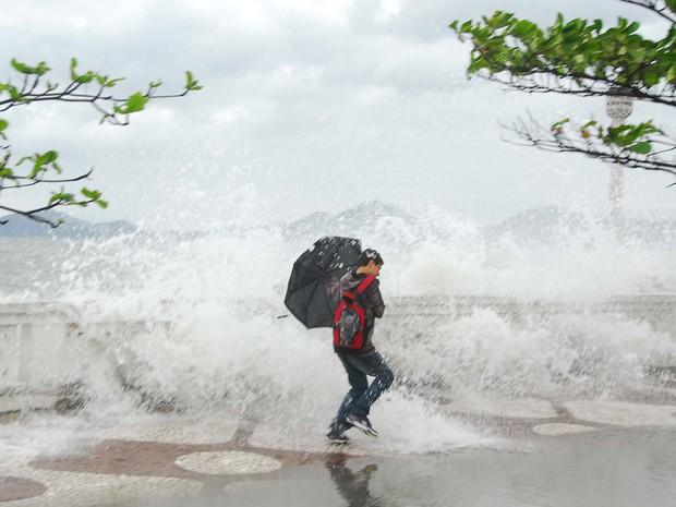 Pedestre é atingido por ondas que invadiram a calçada na ressaca do mar em Santos, no litoral de São Paulo. (Foto: Mário Viola/Futura PRess/AE)