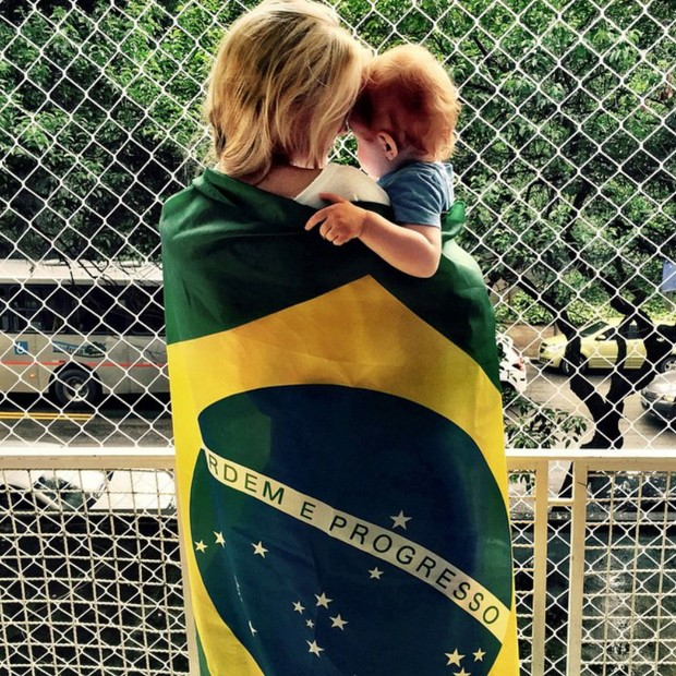Carol Trentini com o filho enrolada na bandeira do Brasil (Foto: Reprodução Instagram)