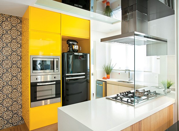 """O armário com laca brilhante amarelo gema deu o ar moderno à cozinha que é aberta para a sala. """"É uma cor divertida que faz uma contraposição equilibrada com o aço inox e o preto dos eletrodomésticos"""", diz a arquiteta Beatriz Quinelato (Foto: Luis Gomes/Casa e Jardim)"""