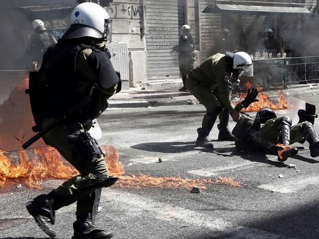 Policial ajuda um colega atingido pelas chamas de um coquetel Molotov durante os conflitos na praça central de Atenas, na Grécia. (Foto: Yorgos Karahalis/Reuters)