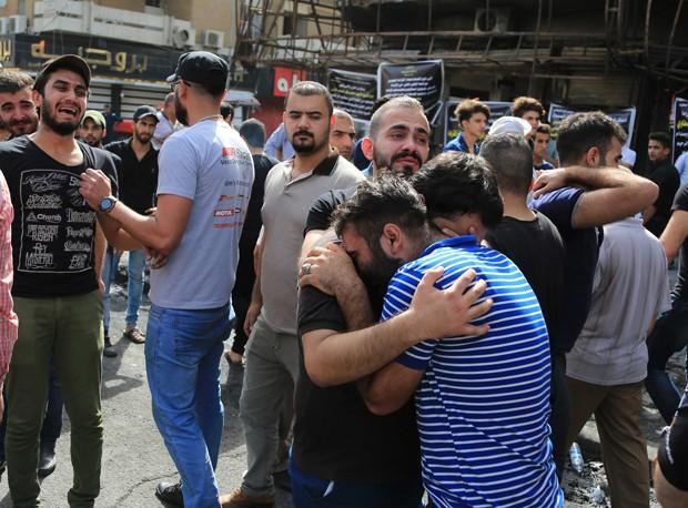 Amigos e parentes choram durante funeral de Akram Hadi, de 24 anos, que morreu no atentado em Bagdá, no Iraque (Foto: Karim Kadim/AP)