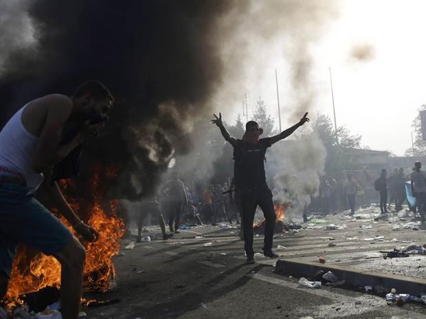 Migrante abre os braços em meio à fumaça de barricadas e de bombas de gás-lacrimogêneo durante confronto entre polícia e migrantes na fronteira entre Sérvia e Hungria perto de Roszke, na Hungria. A polícia húngara passou a barrar a entrada de migrantes (Foto: Stoyan Nenov/Reuters)