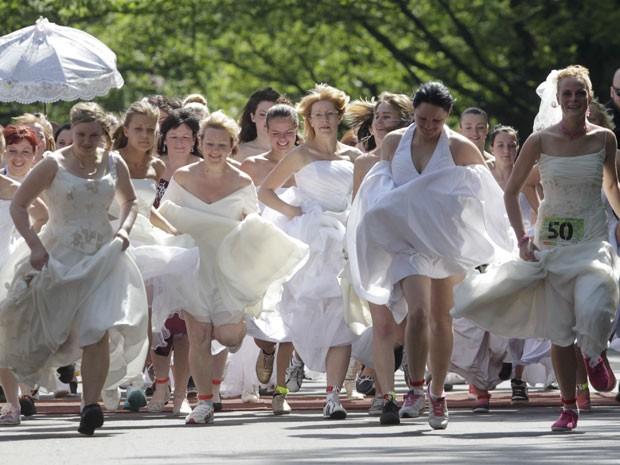 Mulheres participam da competição 'Noiva em fuga' neste sábado (1º) em Riga (Foto: Ints Kalnins/Reuters)
