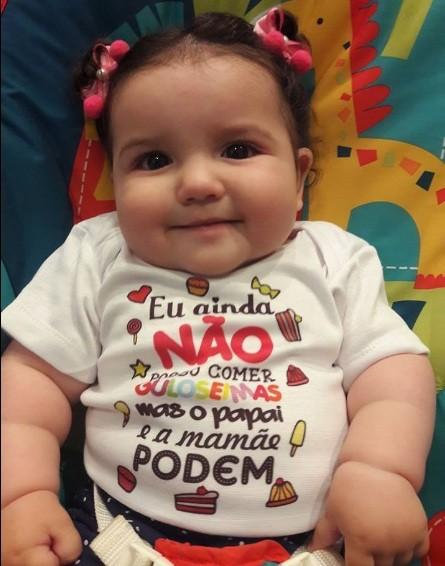 """Menina vestindo body com a frase: """"Eu ainda não posso comer guloseimas, mas o papai e a mamãe podem"""" (Foto: Facebook)"""