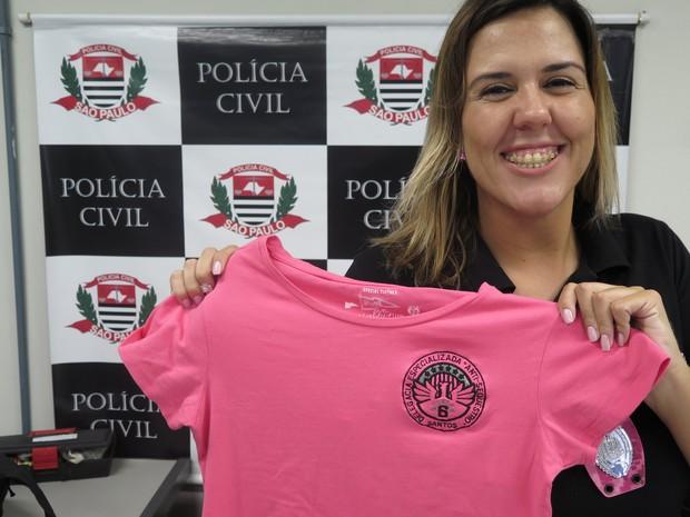 Katherine mostra a blusa rosa da polícia que ganhou dos colegas (Foto: Mariane Rossi/G1)
